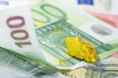 Hundra eurosedel med guld- klumpar stänger sig upp Arkivbilder