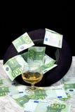 Hundra eurosedlar med ett exponeringsglas för svart hatt av konjak Arkivfoton