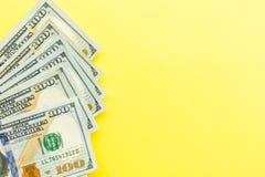 Hundra kassa för dollarräkningar som ligger på gul bakgrund finansiell aff?rsid? Lägenheten lägger, modellen, uppe i luften royaltyfri foto