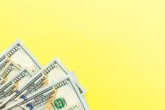 Hundra kassa för dollarräkningar som ligger på gul bakgrund finansiell aff?rsid? Lägenheten lägger, modellen, uppe i luften royaltyfria bilder