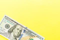 Hundra kassa för dollarräkningar som ligger på gul bakgrund finansiell aff?rsid? Lägenheten lägger, modellen, uppe i luften arkivfoto