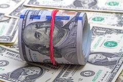 Hundra nya dollar rullar upp med rött gummi Arkivbilder