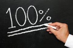 Hundra procent prestation av ett mål på kritasvart tavla royaltyfri bild