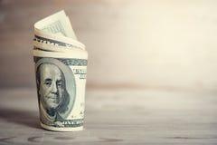 Hundra rullande dollarräkningar Arkivbild