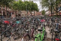 Hundratals cyklar som parkeras i fyrkant av Amsterdam med molnig himmel Fotografering för Bildbyråer