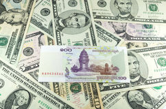 Hundred Cambodian Riel (KHR) on many dollars background. USD, KHR Stock Photos
