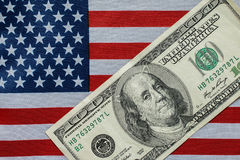 A hundred dollar on the American flag. A hundred dollar bill in front of the American flag Royalty Free Stock Image