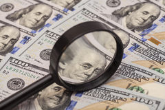 Hundred dollar banknote under magnifying glass Stock Photography