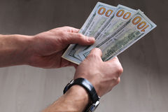 Hundred dollar banknotes in man's hands Stock Photos