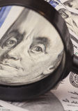Hundred dollar banknotes under magnifying glass Stock Photos