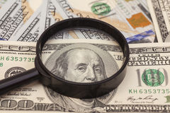 Hundred dollar banknotes under magnifying glass Stock Photo