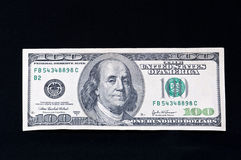 Hundred dollar bill on black Royalty Free Stock Photos