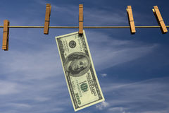 Hundred dollar bill hanging on a clothesline. One hundred dollar bill hanging on a clothesline in front of a cloudy sky Stock Images