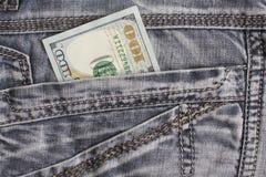 Hundred dollar bill inside back pocket jeans Stock Images