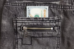 Hundred dollar bill inside back pocket jeans. Hundred dollar bill inside back pocket gray jeans Royalty Free Stock Photography
