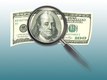 Hundred dollar bill and magnifying glass Royalty Free Stock Image