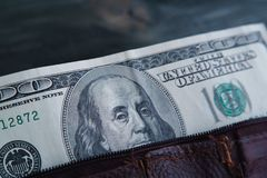 Hundred dollar bill in old shabby leather wallet on wooden table. Close up Royalty Free Stock Photography