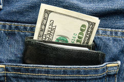 Hundred dollar bill sticks out of a wallet Stock Photo