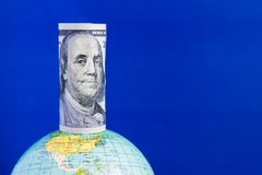 A hundred-dollar bill on top of the globe on a blue background. With copy space. Concept Stock Images