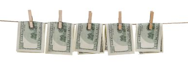 Hundred dollar bills bent in half, attached with clothespins to a rope, isolated on white background. stock image