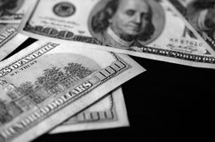 Hundred dollar bills on a dark background, black and white Royalty Free Stock Photos