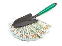 Hundred-dollar bills and garden shovel Stock Images