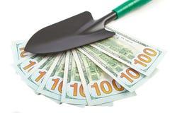 Hundred-dollar bills and garden shovel Stock Photos