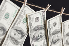 Hundred Dollar Bills Hanging From Clothesline on Dark Background Stock Photo