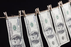Hundred Dollar Bills Hanging From Clothesline on Dark Background Royalty Free Stock Photo
