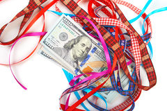 Hundred-dollar bills lying on a pile. Of gift ribbons Royalty Free Stock Photos