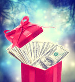 Hundred dollar bills in the red present box. At magic night Stock Image