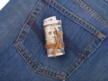Hundred-dollar bills rolled and tied with a rope on the backgrou. Nd of the back pocket of jeans Royalty Free Stock Photography