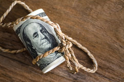 Hundred dollar bills rolled up with  rope. On wooden table : copy space Royalty Free Stock Photography
