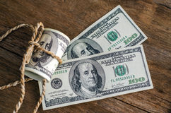 Hundred dollar bills rolled up with rope Royalty Free Stock Photos