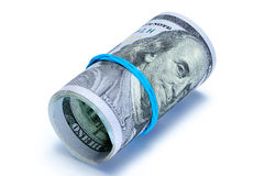 Hundred dollar bills rolled up with rubber band. Pack of banknotes of 100 US dollars is curtailed as a tube and fixed by an elastic band on a white background Royalty Free Stock Photo