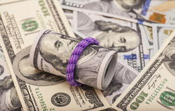 Hundred dollar bills rolled up with rubberband on dollars Royalty Free Stock Image
