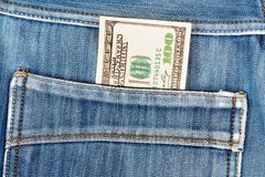 A hundred dollar bills sticking in the back pocket of denim blue Royalty Free Stock Photography