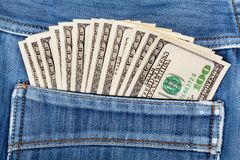A hundred dollar bills sticking in the back pocket of jeans Royalty Free Stock Photo