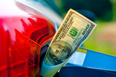 Hundred dollar bills in a vehicle fuel tank neck Royalty Free Stock Photo