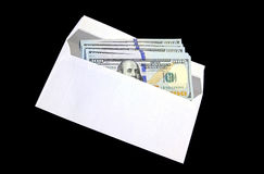 Hundred dollar bills in a white envelope. On a black background Stock Image