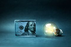 Hundred dollar and light bulb. Concept of idea and wealth Stock Image