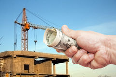 Hundred dollar notes of the USA in a hand against a construction Stock Image