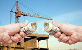 Hundred dollar notes of the USA in a hands against a constructio Royalty Free Stock Photography