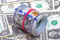 Hundred dollar roll  up with red rubber Stock Image