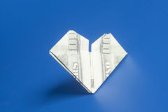 Hundred dollar US bills heart shape origami. On blue Stock Image
