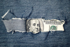 Hundred dollars bill through torn blue jeans texture Stock Image