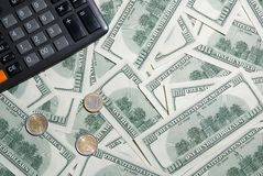 Hundred dollars and euro coins and calculator Royalty Free Stock Images