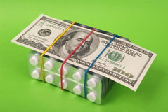 Hundred dollars lays on packing of white tablets Stock Photos