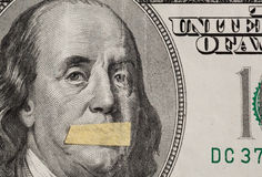 Hundred dollars USA, a symbol of instability of the economy. Silente president, portrait of the American leader Benjamin Franklin with mouth closed on the Stock Photos