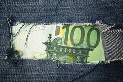 Hundred euros bill through torn blue jeans texture Royalty Free Stock Photography
